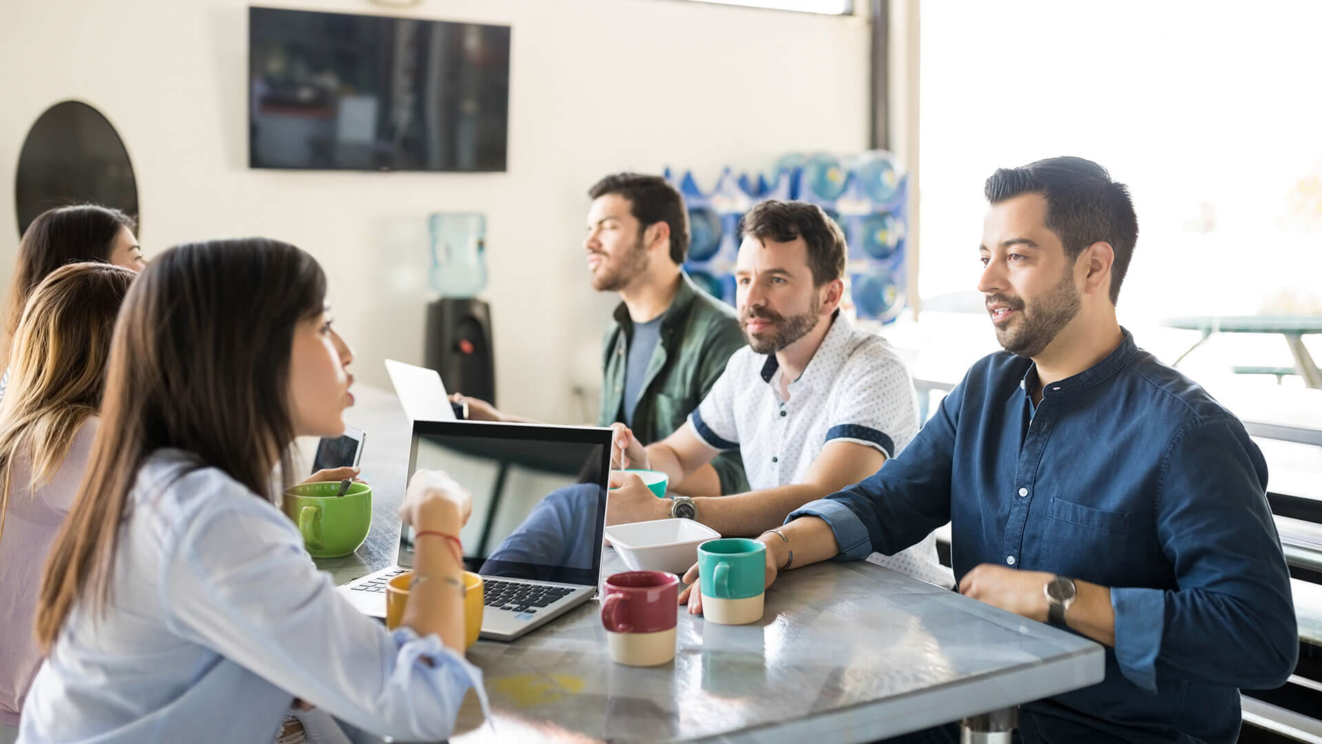 Team culture in the workplace: A group of young professionals sit in discussion around a computer desk